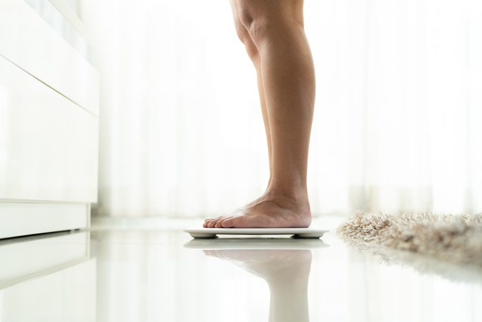 lower section of woman standing on weight scale