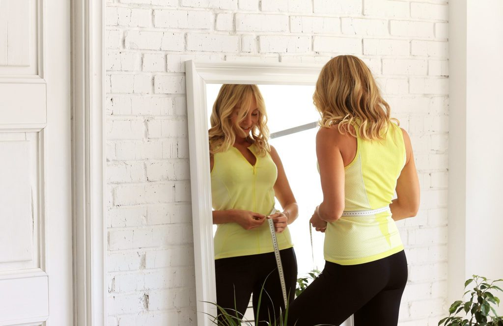 woman measuring waist in mirror