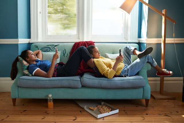 two young women relaxing on couch while looking at smartphones