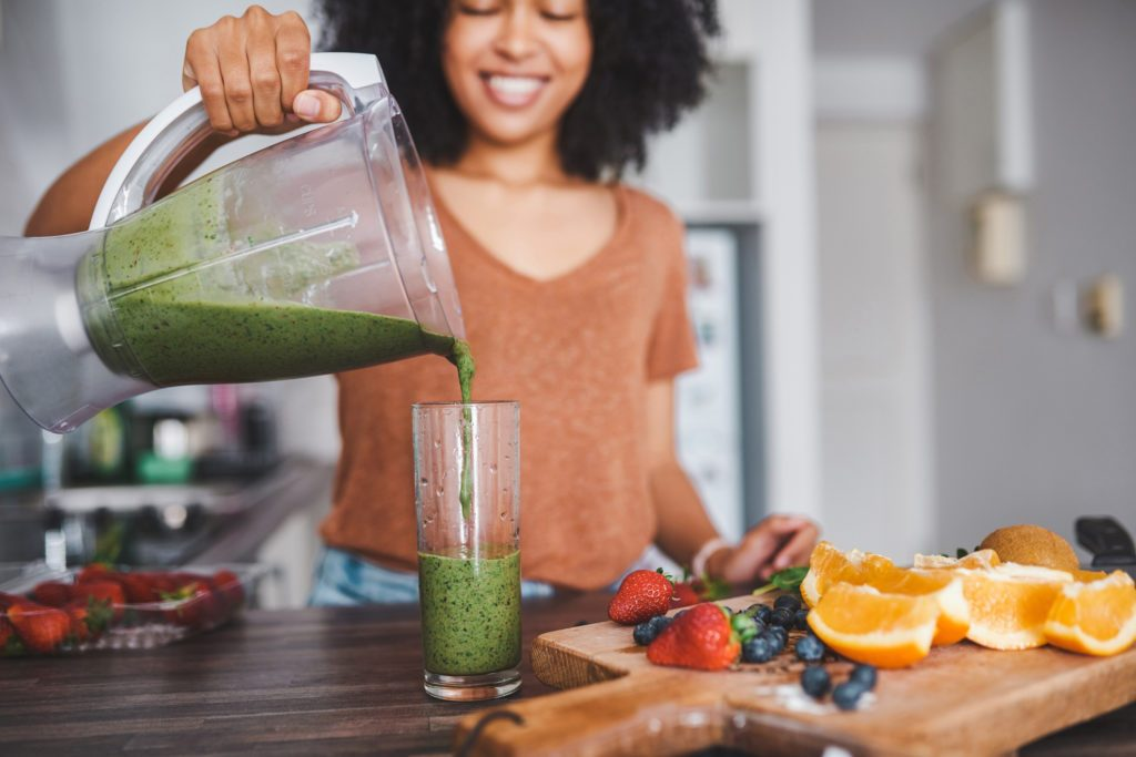 woman pouring healthy smoothie into glass