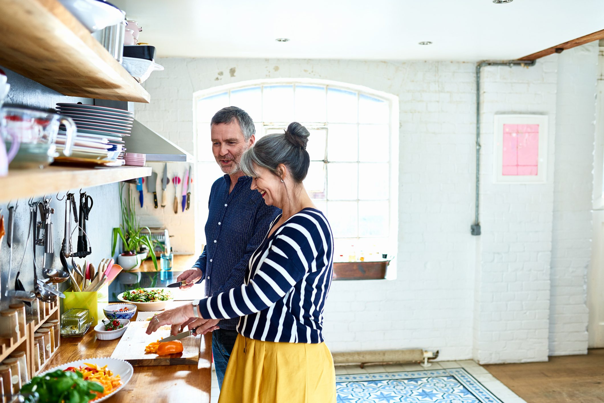 mature couple preparing food together in the kitchen