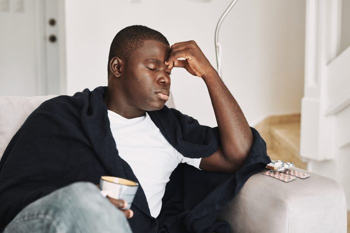 man sitting on couch sick with headache