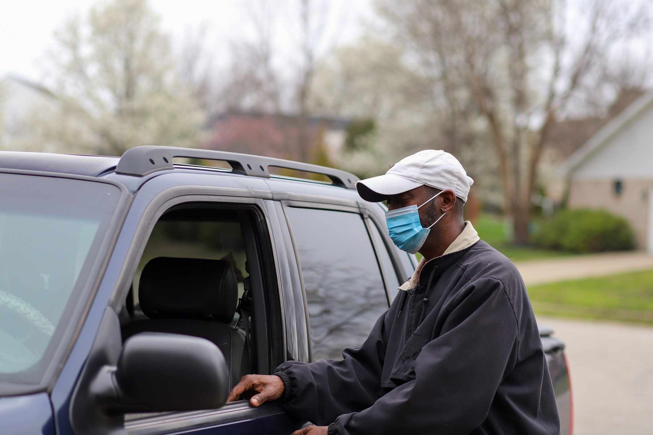 man wearing mask outside getting into car
