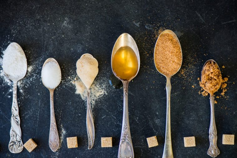 different kinds of sugars in spoons overhead