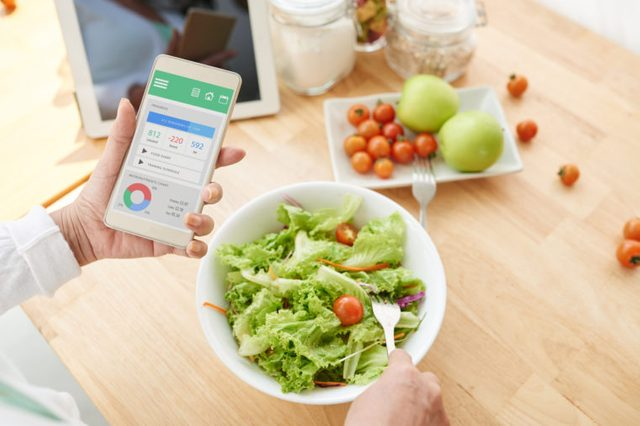 woman counting calories on diet app