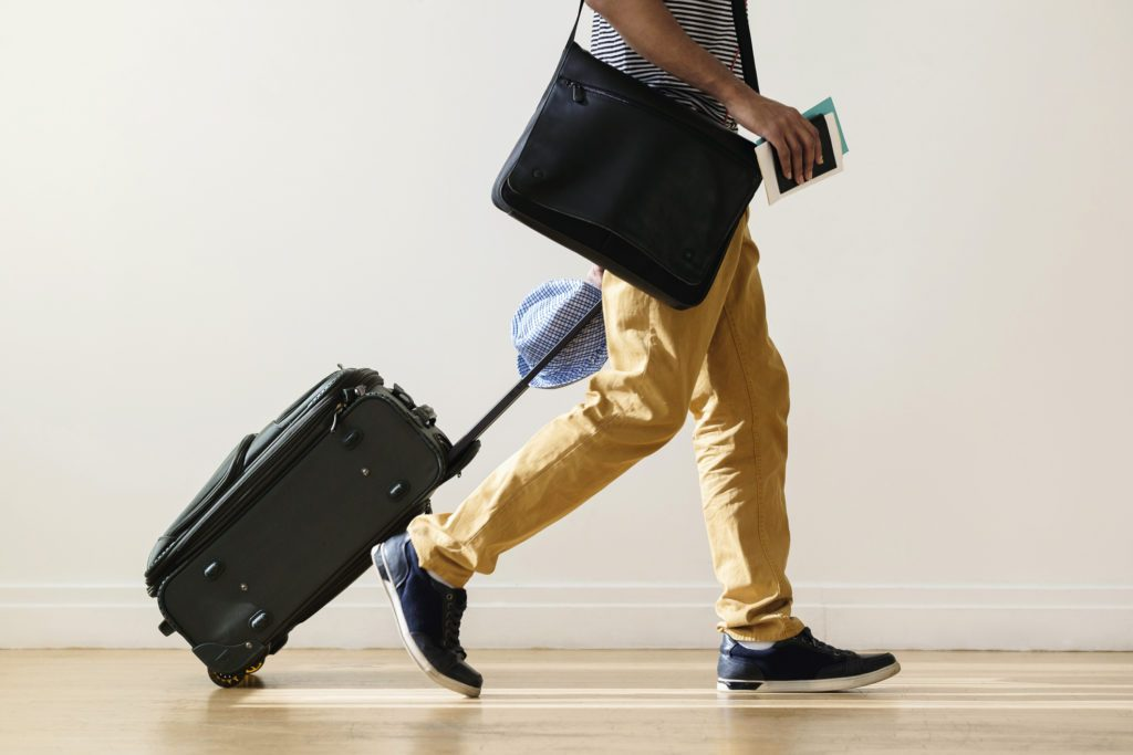 cropped shot of man traveling holding suitcase and passport