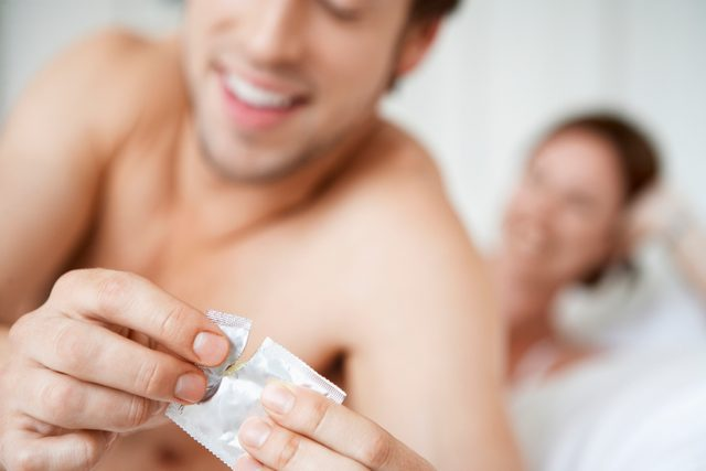couple in bed close up of man opening condom