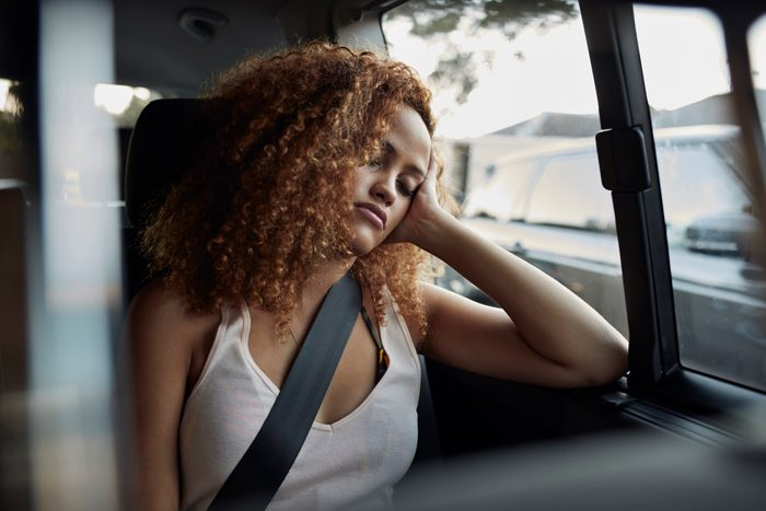 tired young woman in backseat of car