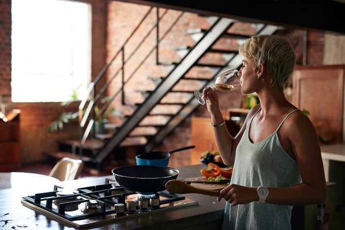 young woman drinking a glass of wine while cooking in the kitchen