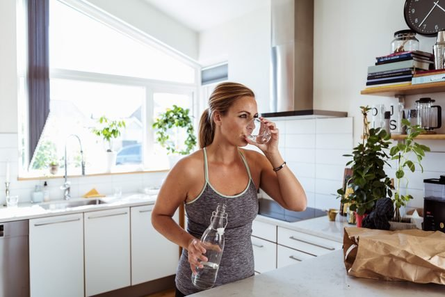 woman drinking water in kitchen