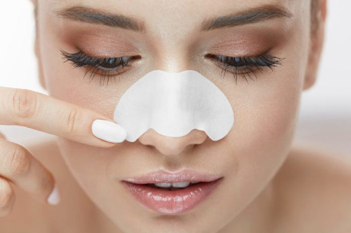 Woman using a pore strip on her nose