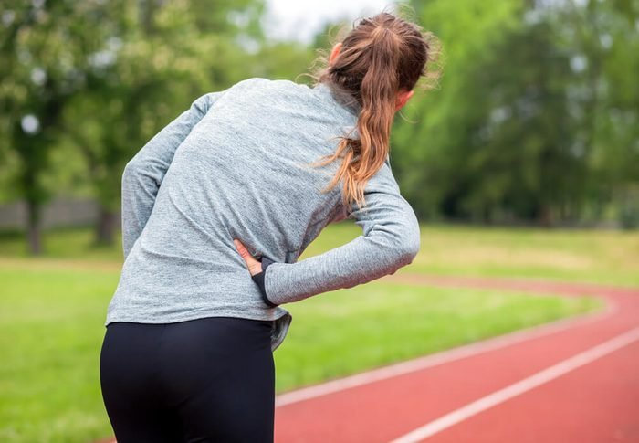 Athletic woman on running track has side cramps during workout