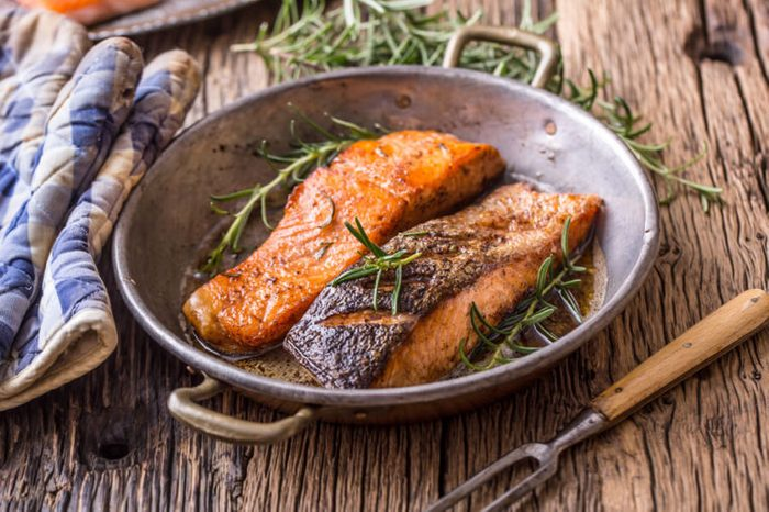 Cooked salmon fillets with rosemary in pan