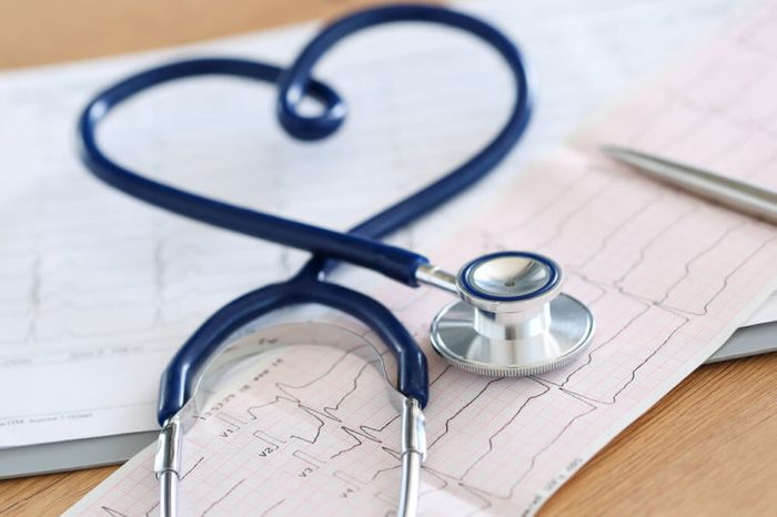 stethoscope twisted in heart shape lying on cardiogram chart closeup