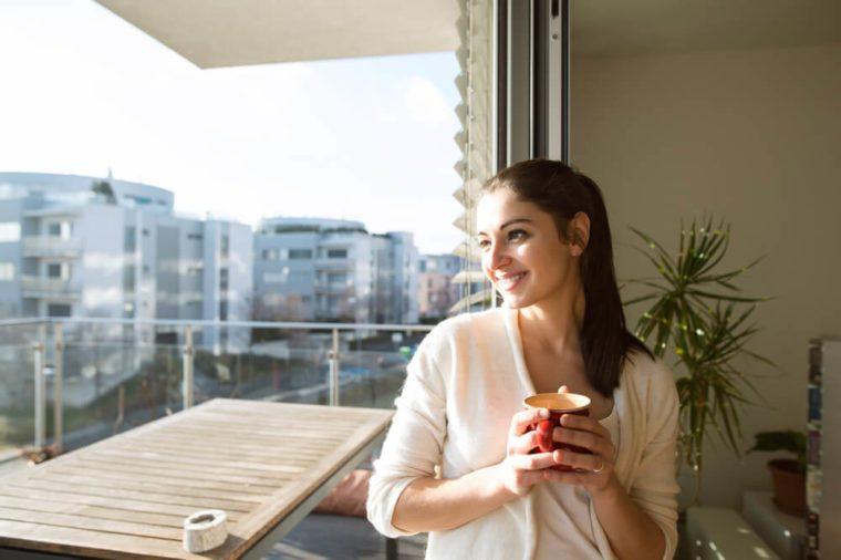 smiling woman on balcony holding mug