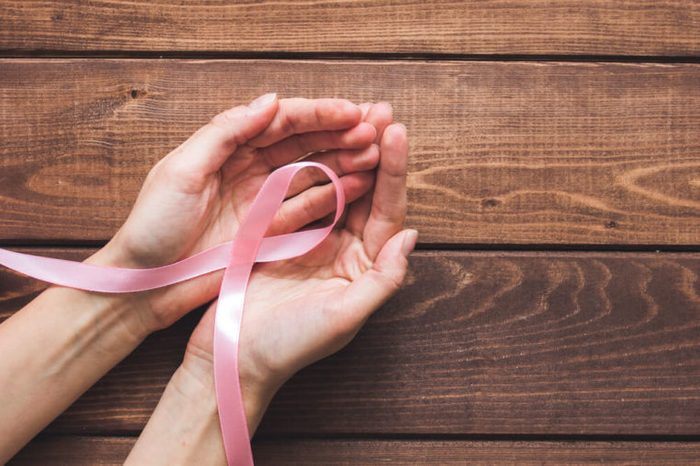 pink ribbon twisted into breast cancer symbol in cupped hands