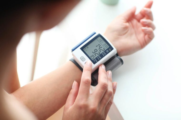 Person with digital blood pressure monitor on wrist