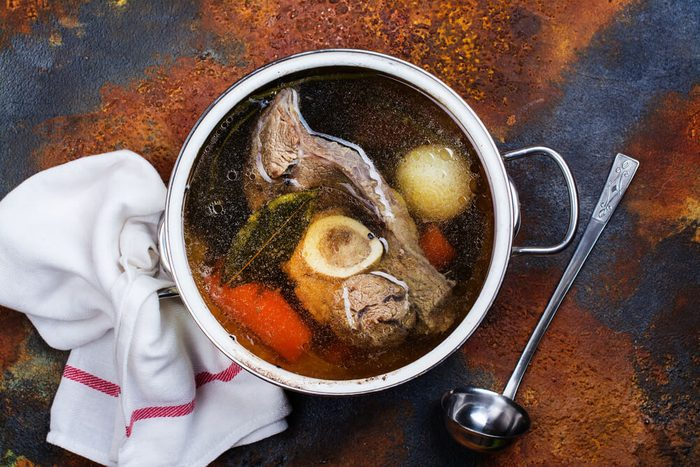 Broth soup in a cooking pot with ladle