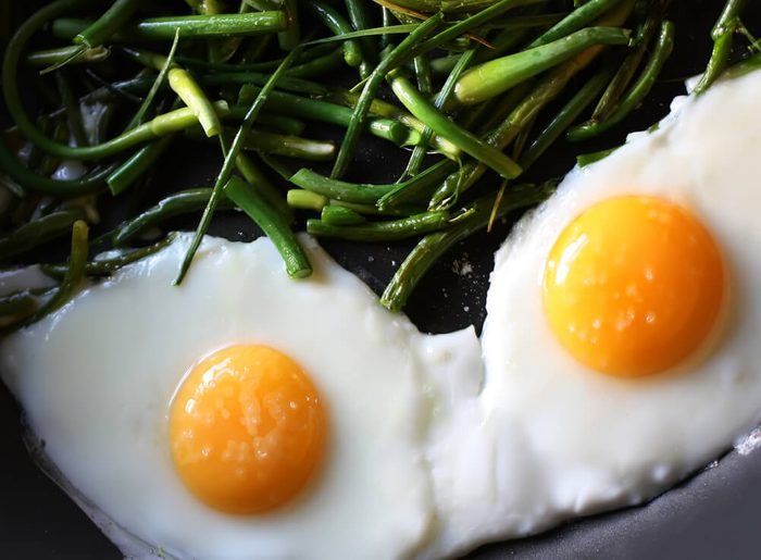 Fried eggs with green beans on the pan