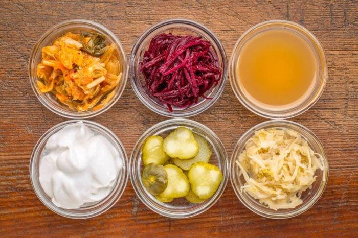 Fermented food great for gut health--glass bowls of kimchi, red beets, apple cider vinegar, coconut milk yogurt, cucumber pickles, sauerkraut