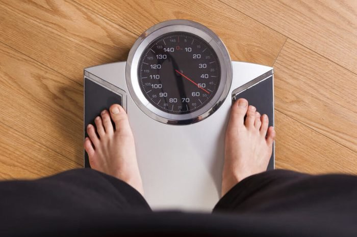 Person weighing himself on a scale