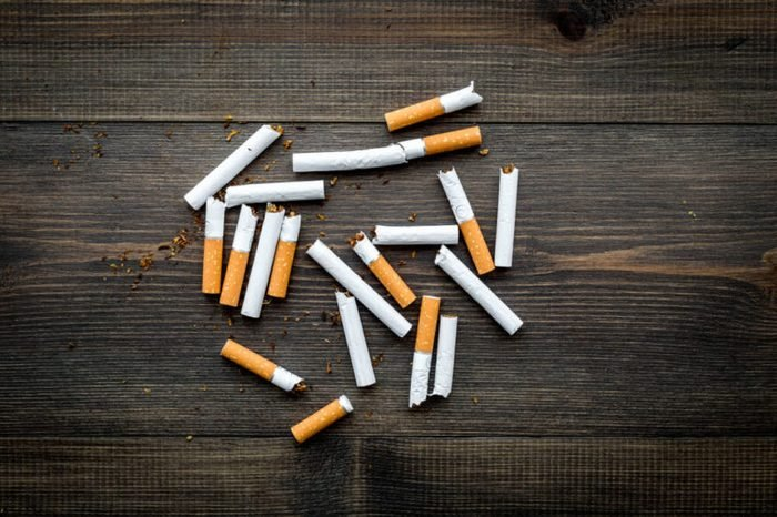 Scattered cigarettes on dark wooden background