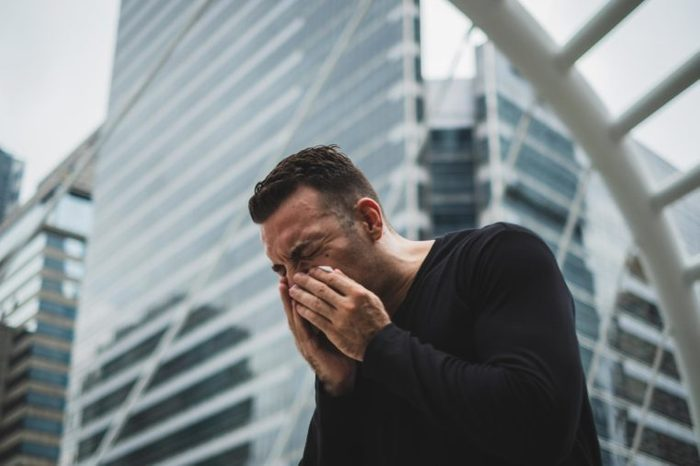 man sneezing city allergies cold sick