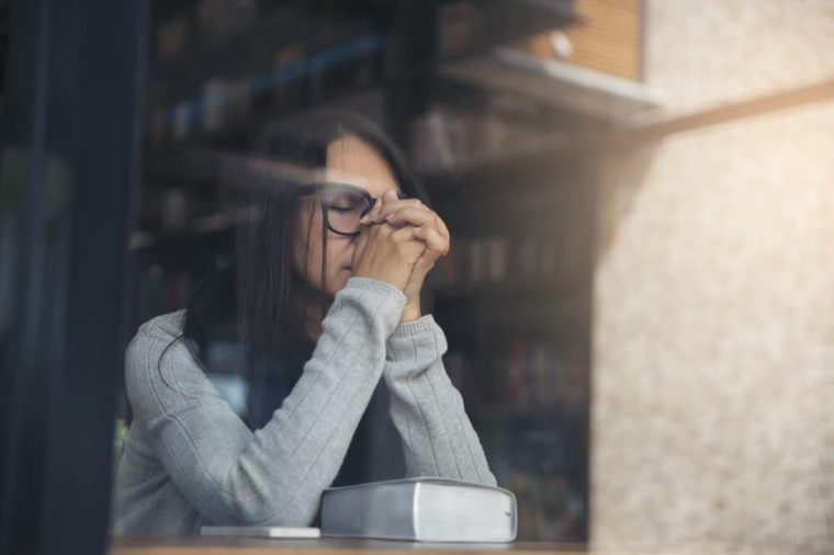 Beautiful woman wearing gray sweater and glasses sitting in a library appearing sad and stressed.