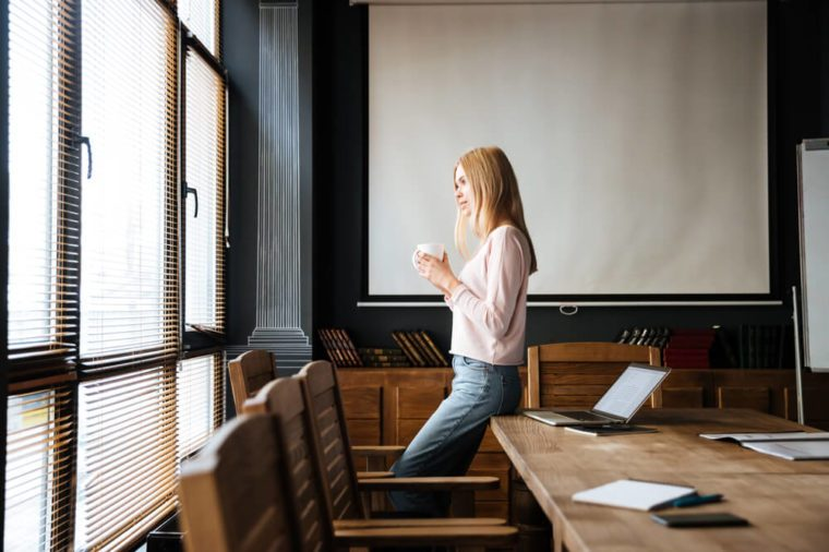 Pretty young lady standing drinking coffee and looking through the boardroom windows.