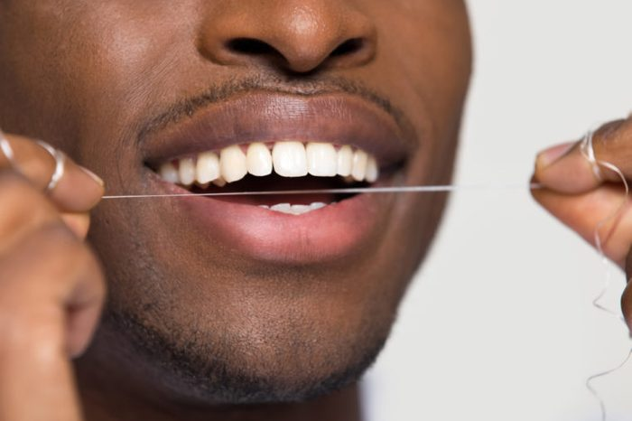 Closeup of a man cleaning white healthy teeth holding using dental floss.