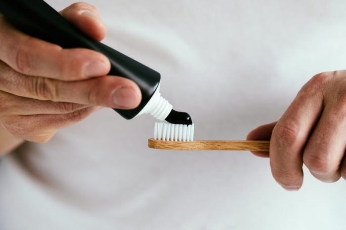 Man with a black charcoal toothpaste and a bamboo toothbrush.