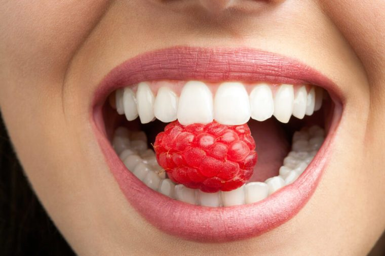 Healthy woman's teeth biting a raspberry.