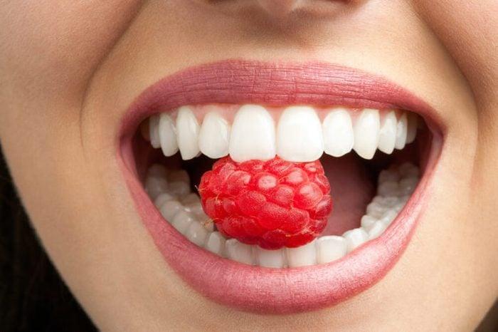 Healthy woman's teeth biting a raspberry.
