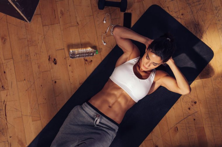 Young woman doing crunches on mat.
