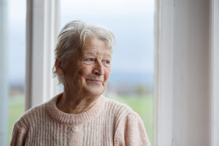 Senior-aged woman looking out the window.