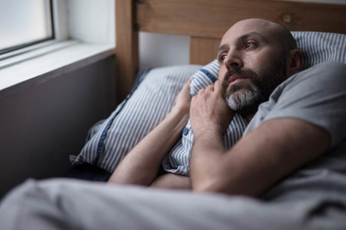 Mid forties depressed man in bed at home.