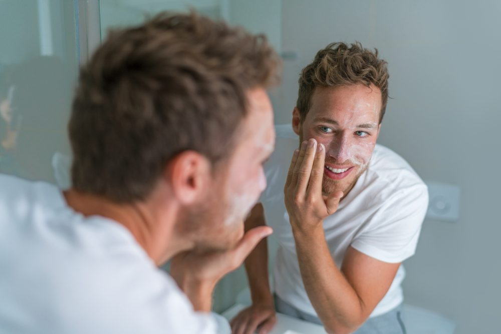 Man washing face with soap scrubbing exfoliation mask