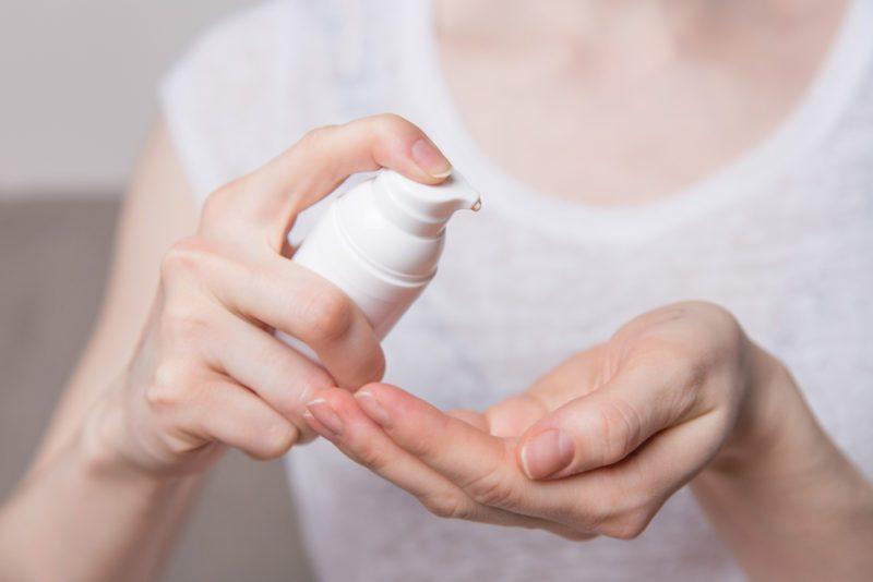 Women's hands using wash hand sanitizer gel pump dispenser.
