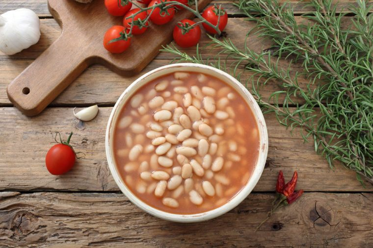 White beans in tomato sauce in a bowl on rustic table background