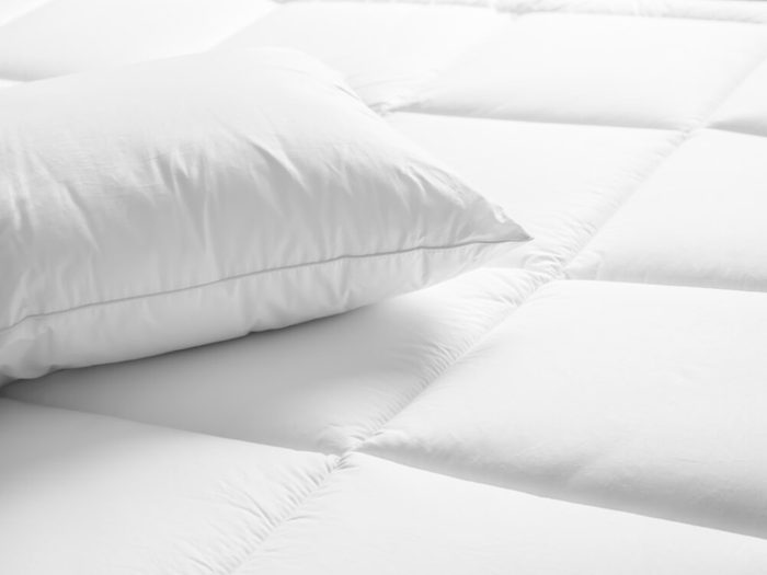 Closeup of white pillow on the bed in the bedroom