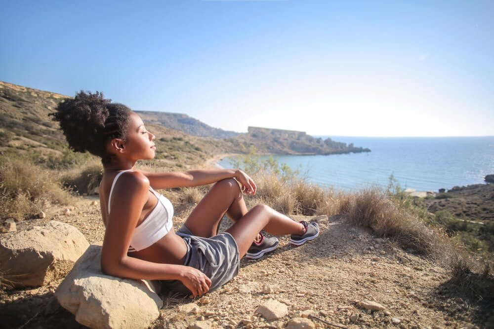 woman relaxing on a cliff, looking the sea