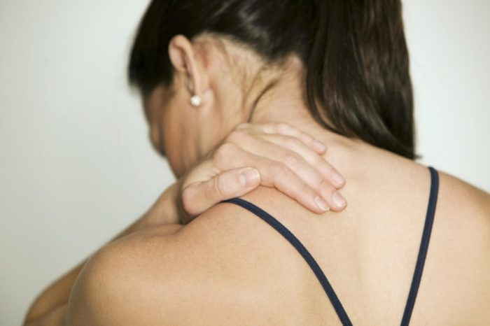 Woman massaging shoulder