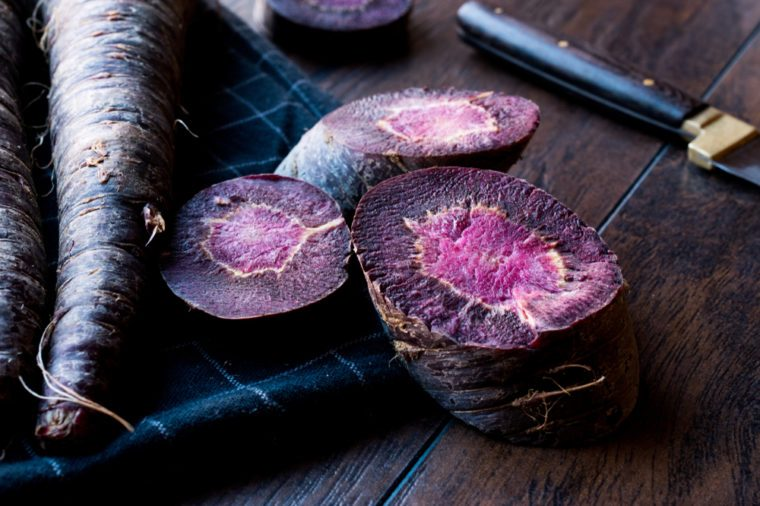 Purple Carrots on Dark Wooden Surface.