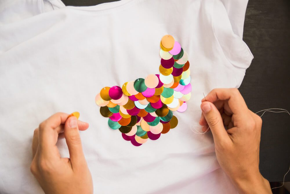 girl decorates white T-shirt with colored sequins for gift