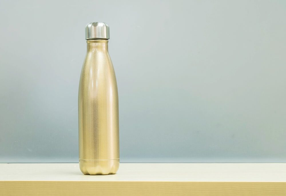 Closeup gold color of aluminium flask for keep hot water on blurred wooden desk