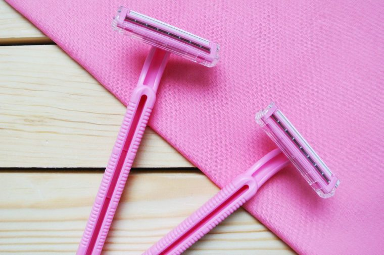 Couple of pink women's disposable razors on wooden table.