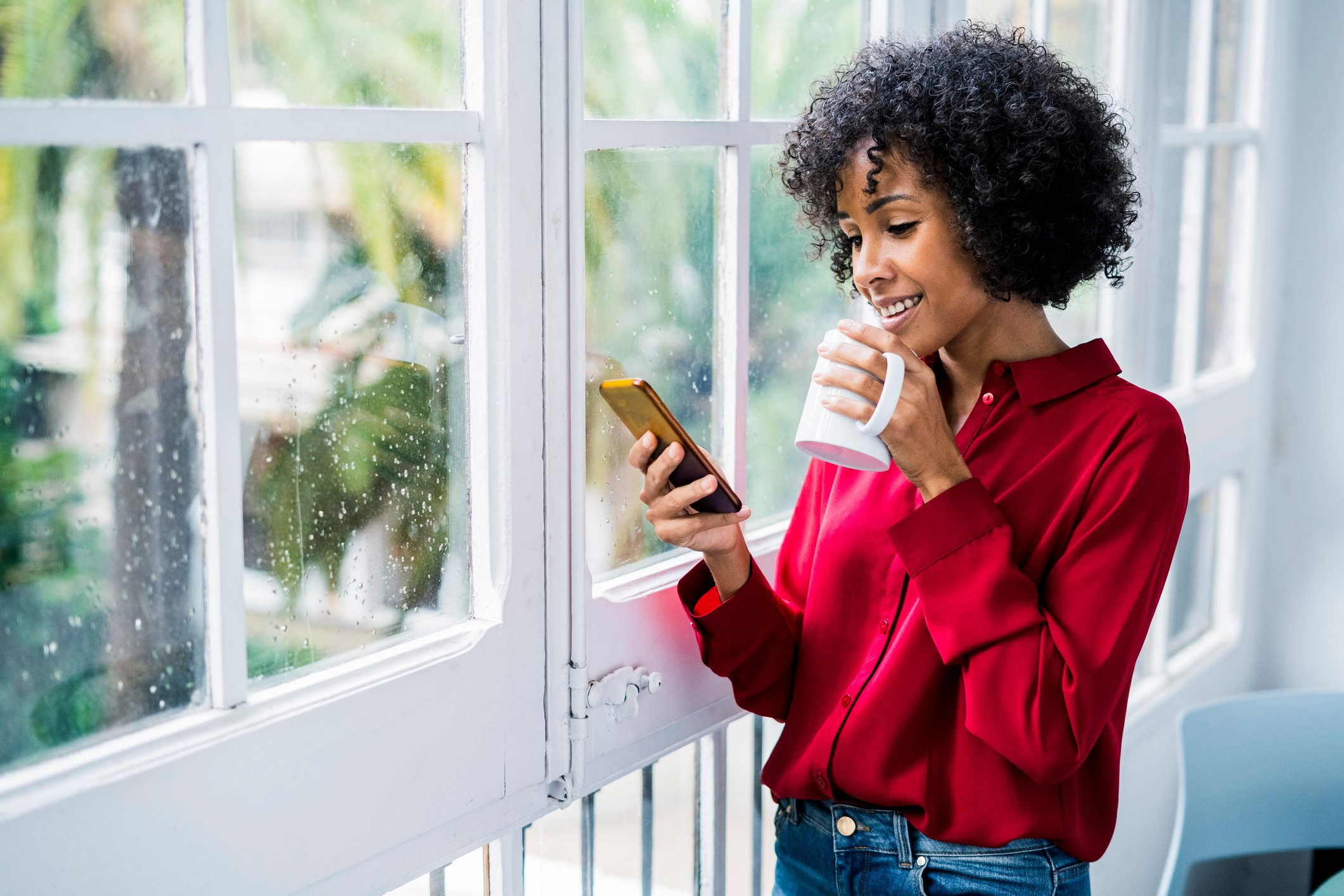 woman drinking a cup of coffee and looking at phone