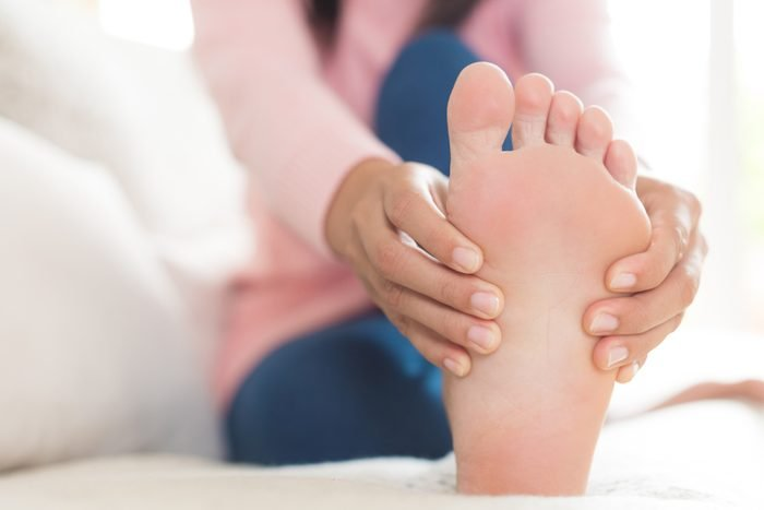 close up of woman holding foot