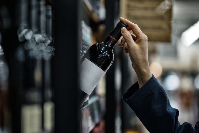close up of woman's hand grabbing wine off of shelf at store