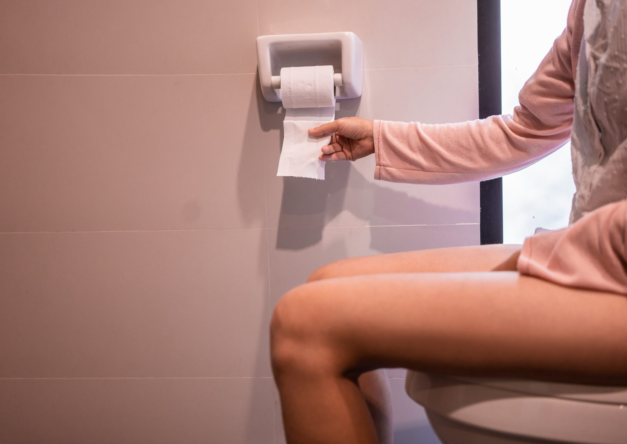woman sitting on toilet grabbing toilet paper